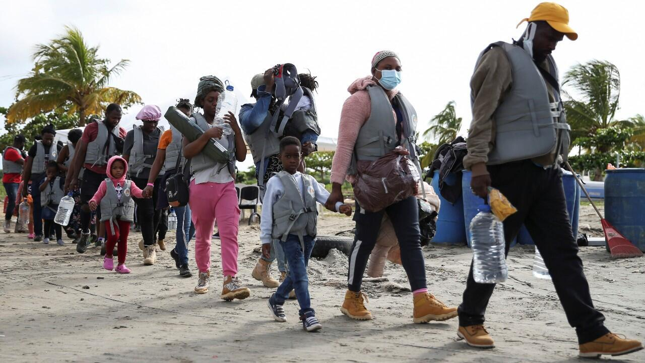 Migrants, mostly Haitians, walk to board boats that will take them to Acandi, to cross to Panama to continue their journey to the United States, in Necoclí, Colombia, on September 23, 2021.