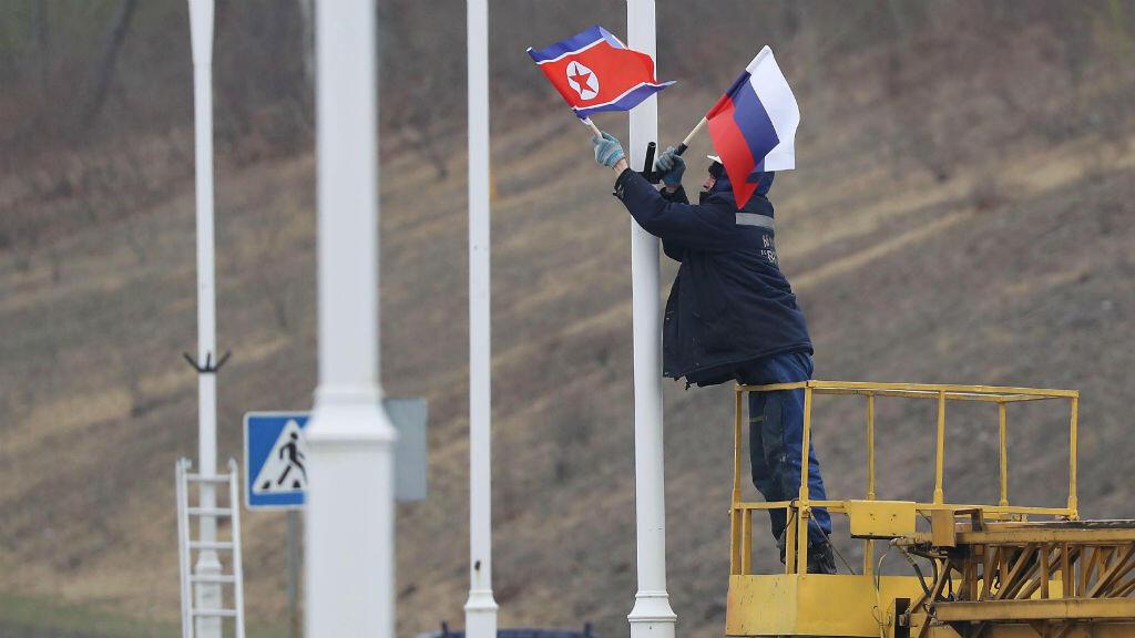 Un empleado coloca sendas banderas de Corea del Norte y de Rusia en las farolas adyacentes a una carretera, en Vladivostok, Rusia, ciudad donde se celebrará la primera cumbre entre Kim Jong-un y Vladimir Putin, el 23 de abril de 2019.