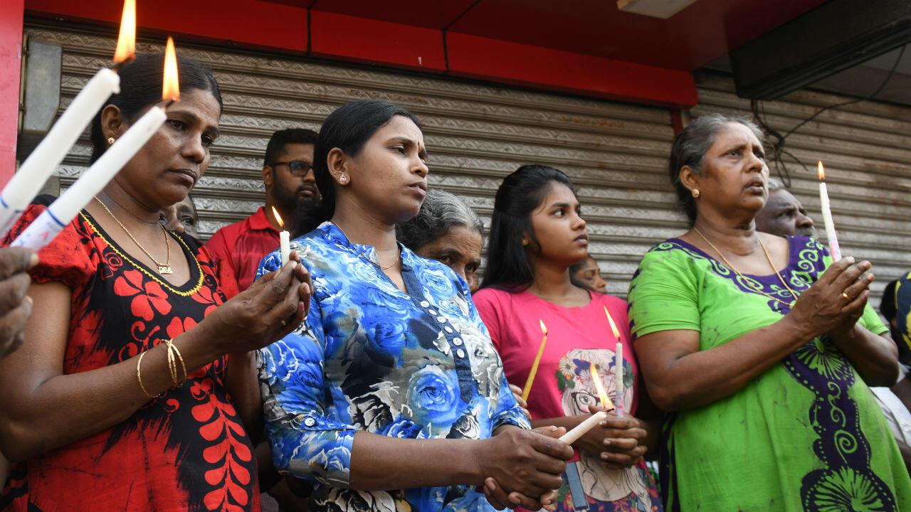 Des Sri Lankais en deuil tiennent une bougie lors de l'hommage aux victimes de l'explosion d'une bombe à Colombo le 23 avril 2019.