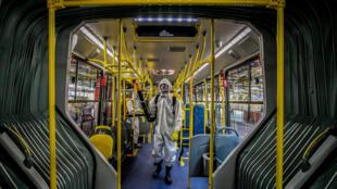 Personal militar de las Fuerzas Armadas brasileñas desinfectan un autobús en la terminal de autobuses de Santa Candida en Curitiba, estado de Paraná, Brasil, el 10 de agosto de 2020