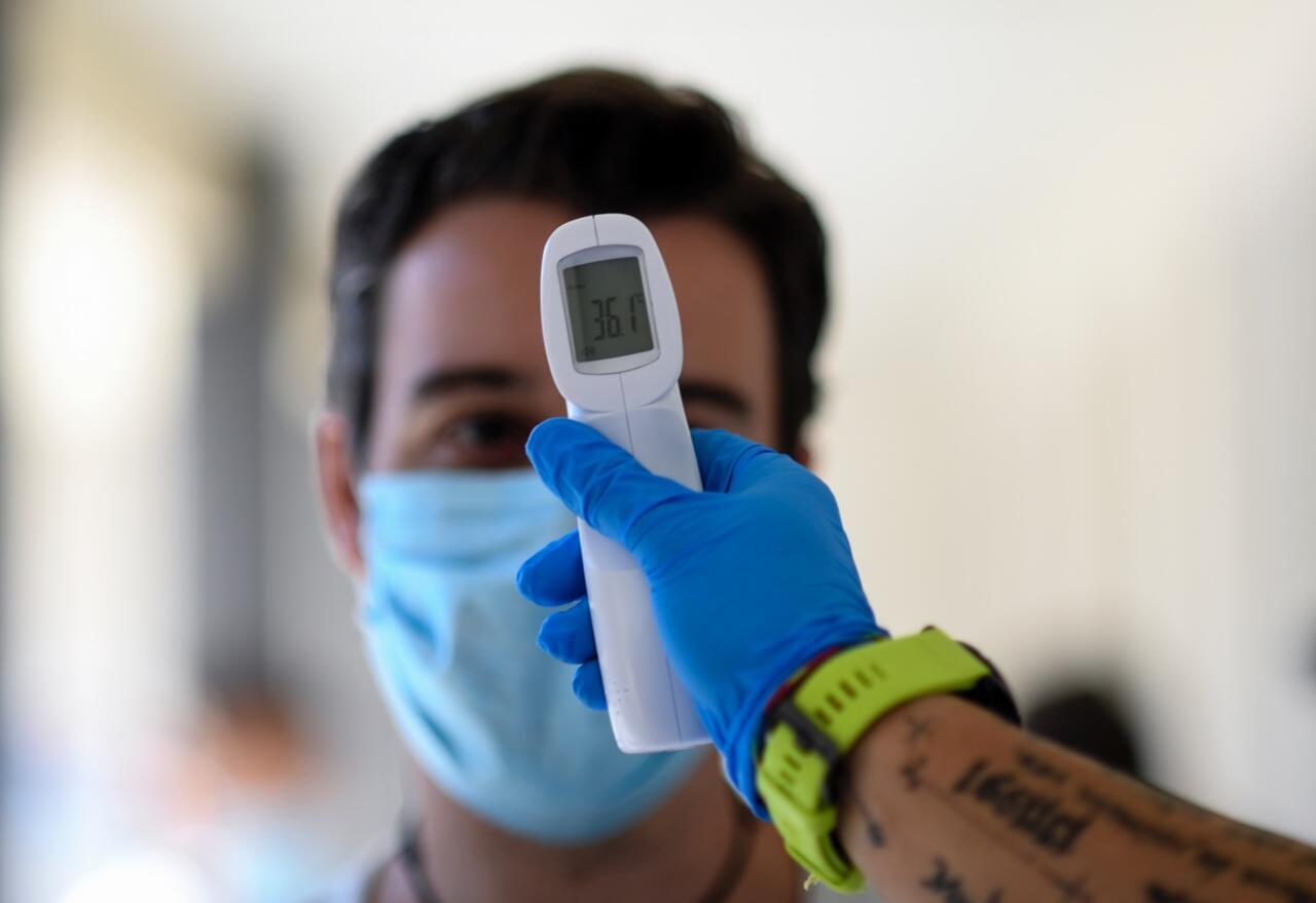 Un trabajador sanitario le toma la temperatura a un hombre en un centro de pruebas de Covid-19 en Madrid, España, el 17 de agosto de 2020.