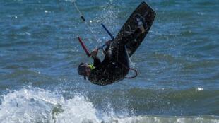 Un surfeur avec son masque profite des joies de la mer à Ladispoli (40 kms de Rome), le 7 mai 2020