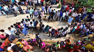 La gente hace fila para emitir sus votos en un colegio electoral durante la tercera fase de los comicios generales en Guwahati, India, el 23 de abril de 2019.