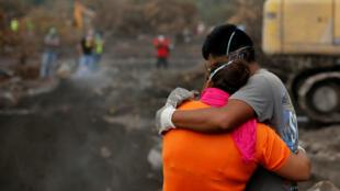 Eva Ascon, sobreviviente, abraza a un miembro de su familia mientras los socorristas buscan a sus seres queridos entre los escombros en San Miguel Los Lotes, Guatemala el 15 de junio de 2018.