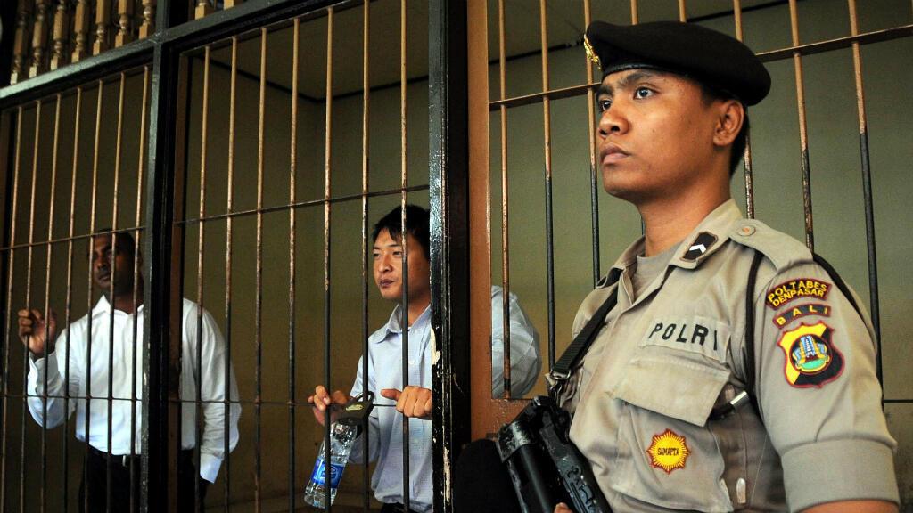Un policier indonésien devant les Australiens Andrew Chan et Myuran Sukumaran, à Bali, le 8 octobre 2010.