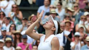 La Roumaine Simona Halep celèbre sa victoire sur l'Américaine Serena Williams à l'issue de la finale du tournoi de Wimbledon, le 13 juillet 2019.