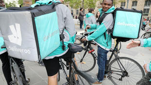 Jacques Demarthon, AFP | Bike couriers working for Deliveroo demonstrate on August 11, 2017 at Place de la République in Paris against the per-delivery contract.