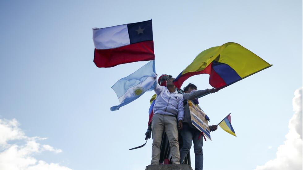 Manifestantes ondean una bandera chilena y otra colombiana durante el tercer paro nacional en Bogotá el 4 de diciembre de 2019