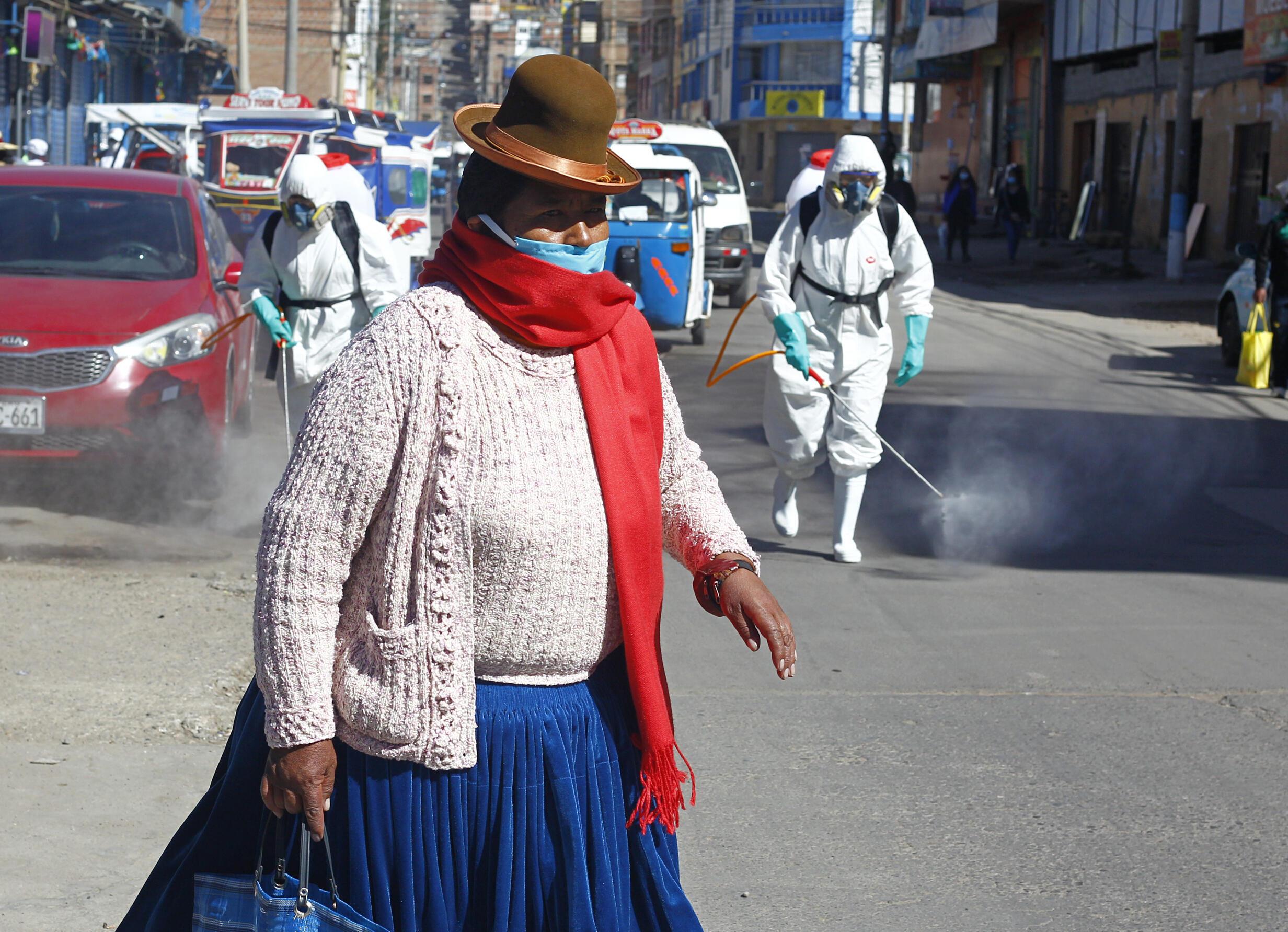 Una mujer con atuendos indígenas típicos aymaras camina cerca de los trabajadores municipales que desinfectan un mercado en Puno, Perú, cerca de la frontera con Bolivia, el 10 de junio de 2020