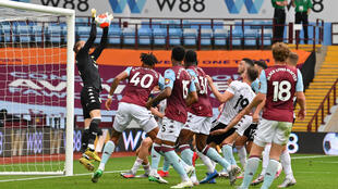 Aston Villa goalkeeper Orjan Nyland jumps to catch the ball before falling back into the goal