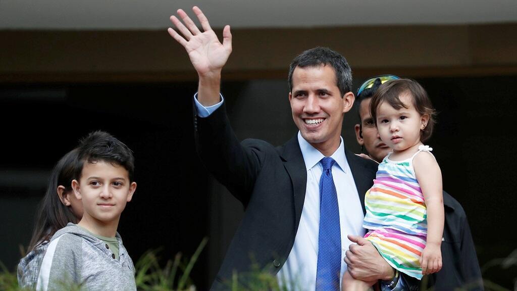 El líder opositor venezolano y proclamado presidente interino Juan Guaidó saluda a sus partidarios mientras lleva a su hija fuera de su casa en Caracas, Venezuela, el 31 de enero de 2019.