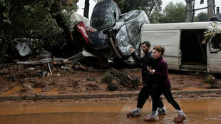 Habitantes de Mandra usan bolsas de plástico para protegerse del barro mientras caminan junto a los automóviles destruidos, tras las inundaciones repentinas del 15 de noviembre que azotaron zonas al oeste de Atenas y causaron la muerte de al menos 16 personas, el 16 de noviembre de 2017.