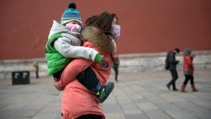 Une femme promène son enfant dans la Cité interdite à Pékin