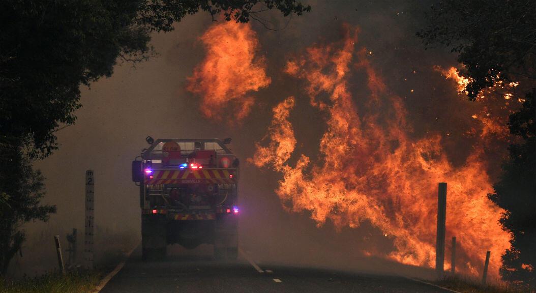 Las llamas alcanzan una carretera cerca a Coffs Harbour, Nueva Gales del Sur, Australia, el 12 de noviembre de 2019.