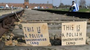 """لافتتان كتب عليهما """"هذا معسكر اعتقال بولندي"""" تركت على سكة حديد خلال المسيرة السنوية إلى معتقل أوشفيتز بيركناو في بولندا في 12 أبريل 2018"""