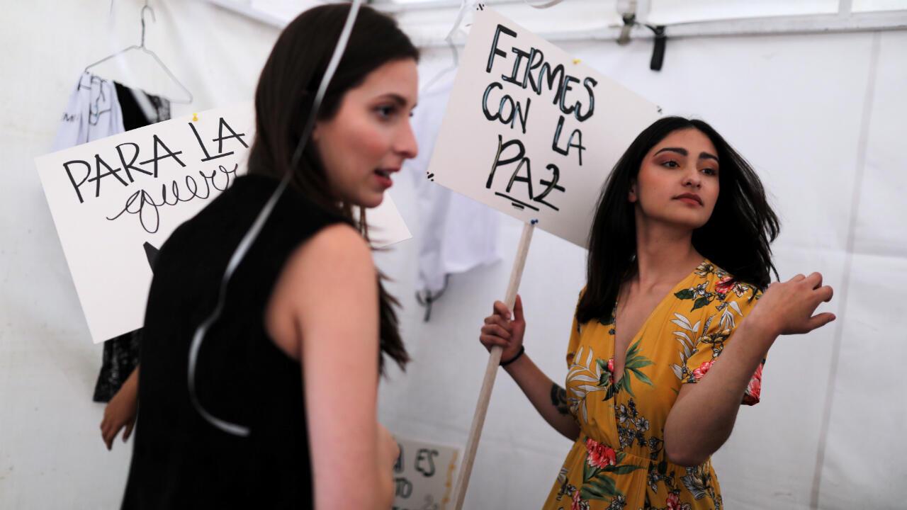 Los carteles fueron escritos por los excombatientes en defensa del acuerdo que firmaron con el Estado en 2016 y acompañaron a las modelos en pasarela delante de un abultado público de profesores y estudiante.