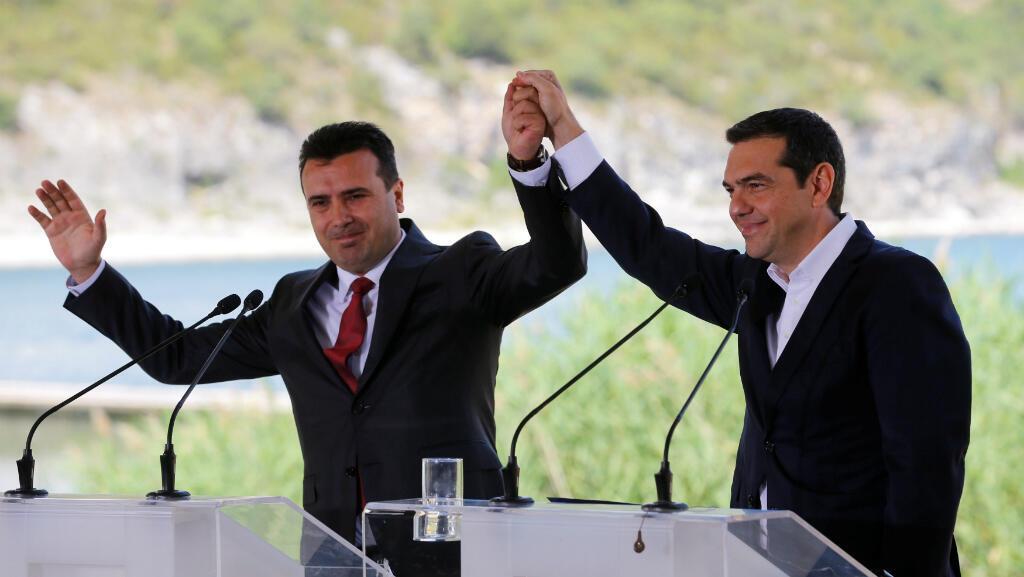 El primer ministro griego Alexis Tsipras y el primer ministro macedonio, Zoran Zaev, hacen un gesto antes de la firma de un acuerdo que ponía fin a la disputa sobre el nombre de la ex República Yugoslava en el pueblo de Psarades, en Prespes, Grecia. 17 de junio de 2018.
