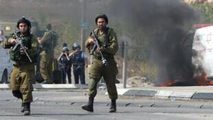 Des soldats israéliens sur le site d'un incident impliquant un conducteur israélien, le 20 octobre 2015 à Hébron.