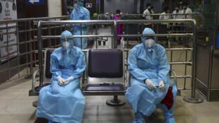 Personal sanitario aguarda la llegada de un vuelo con ciudadanos indios evacuados de Dubái, el 9 de mayo de 2020 en el aeropuerto de Chennai, al este de India