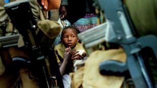 Foto de archivo de una niña hutu que se sienta tensa entre una multitud de 10.000 refugiados ruandeses que fueron detenidos para cruzar a República Democrática del Congo, después de que la frontera se cerrara, el 21 de agosto de 1994.