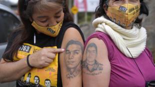 """Las colombianas Beatriz Mendez y Doris Tejada, cuyos hijos desaparecieron hace 12 años, usan mascarillas en las que se lee """"¿Quién dio la orden?"""" y muestran los tatuajes de sus hijos, en medio de la pandemia por el coronavirus"""