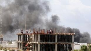 Trabajadores de una obra de construcción observan mientras el humo se eleva tras una explosión en Mogadiscio, Somalia, el 22 de julio de 2019.