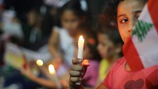 طفلة تحمل شمعة والعلم اللبناني.