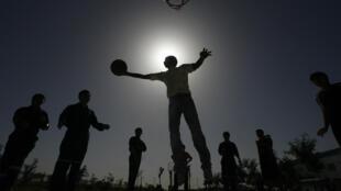 Los trabajadores de una fábrica en Korla, en la región china de Xinjiang juegan al baloncesto durante una pausa el 10 de octubre de 2006