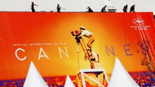 Un grupo de trabajadores despliega el cartel oficial de la edición 72 del Festival de Cannes el 12 de mayo de 2019.