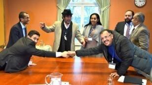 العضو في وفد الحوثيين عبد القادر مرتضى (يسار) والعضو في الوفد الحكومي عسكر زعيل يتصافحان خلال المحادثات حول اليمن في مدينة ريمبو السويدية في 11 كانون الأول/ديسمبر 2018
