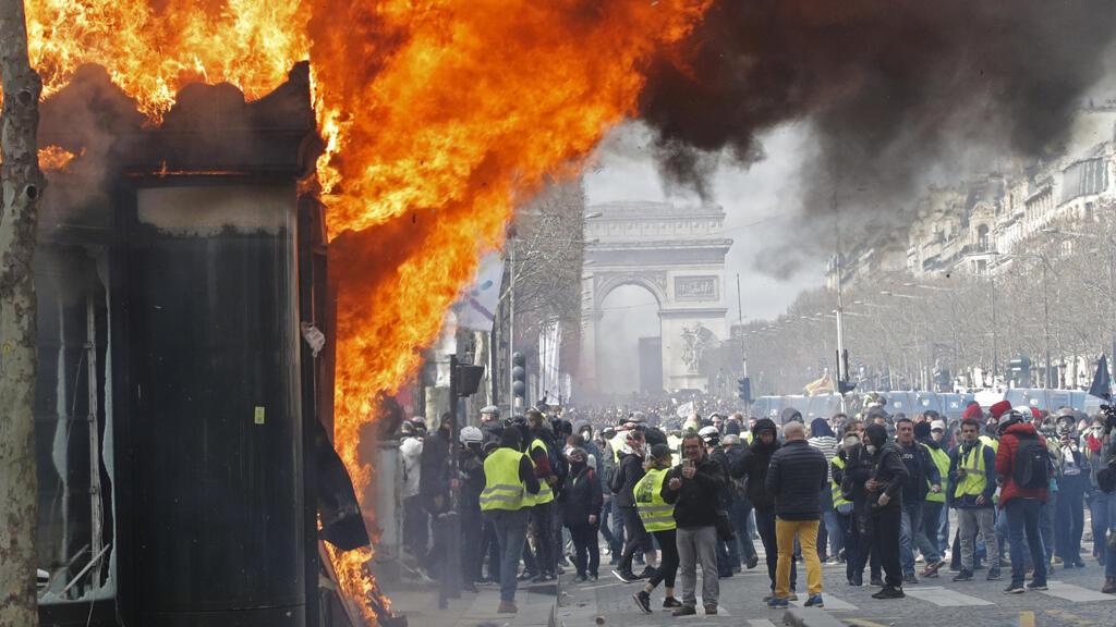 Una tienda de prensa en llamas se ve durante una manifestación del movimiento 'chalecos amarillos' en París, Francia, el 16 de marzo de 2019.