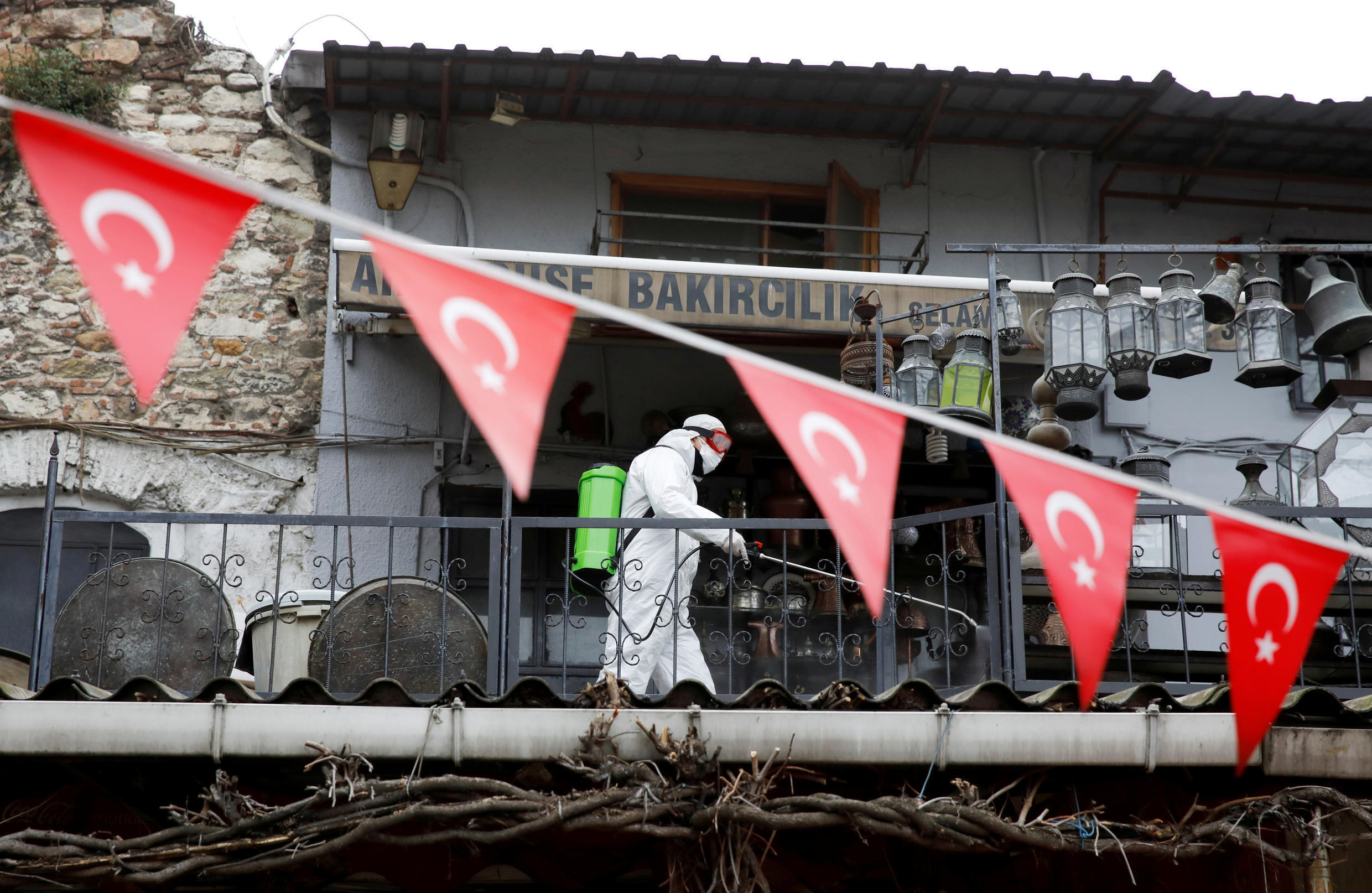 A worker in a protective suit sprays disinfectant at Grand Bazaar, known as the Covered Bazaar, to prevent the spread of coronavirus disease, in Istanbul, Turkey, March 25, 2020.