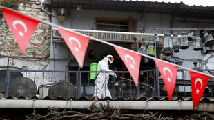 A worker in a protective suit sprays disinfectant at Grand Bazaar, known as the Covered Bazaar, to prevent the spread of coronavirus disease (COVID-19), in Istanbul, Turkey, March 25, 2020.