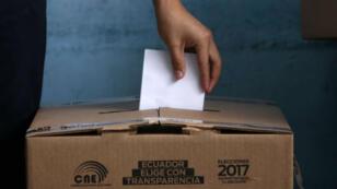 Une femme glisse son bulletin de vote dans une urne, le dimanche 2 avril 20147, à Quito, en Équateur.