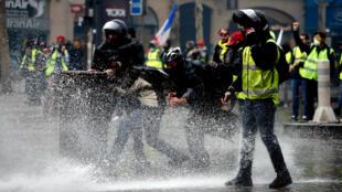 Manifestantes con chalecos amarillos, un símbolo de la protesta de los conductores franceses contra la subida de los precios de la gasolina, reciben el golpe de un cañón de agua de la policía en los Campos Elíseos en París, Francia, el 24 de noviembre de 2018.