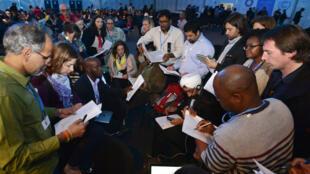 Des représentants d'ONG lisent la proposition d'accord présentée par le ministre péruvien de l'Environnement Manuel Pulgar Vidal, le 13 décembre 2014.
