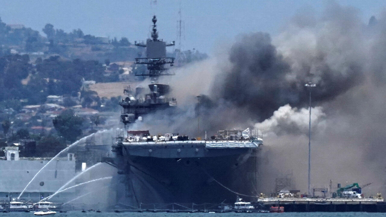 Firefighting boats spray water onto the U.S. Navy amphibious assault ship USS Bonhomme Richard as smoke rises from a fire onboard the ship at Naval Base San Diego, as seen from Coronado, California, U.S. July 12, 2020.