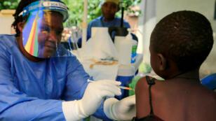 Une infirmière ougandaise vaccine un enfant à Kirembo, près de la frontière avec la RD Congo, le 16 juin 2019.