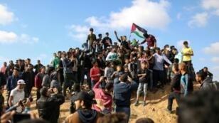 فلسطينيون يرفعون علمهم خلال تظاهرة في ذكرى يوم الأرض قرب الحدود مع إسرائيل شرق مدينة غزة في 30 آذار/مارس 2018