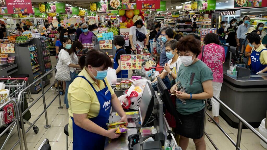 Decenas de personas esperan en fila durante sus compras en un supermercado de Hong Kong, donde los rebrotes de Covid-19 golpean con fuerza. El 27 de julio de 2020.