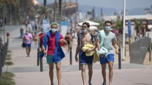 Des promeneurs avec des masques le long de la plage à Barcelone, le 18 juillet 2020