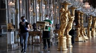 A worker carries furniture in the Hall of Mirrors of the Palace of Versailles near Paris on June 5, 2020, on the eve of its re-opening after 82 days of closure due to the coronavirus outbreak.