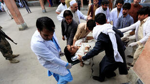 Hombres afganos llevan a un hombre herido a un hospital después de un ataque suicida, en Jalalabad, Afganistán, 2 de octubre de 2018.