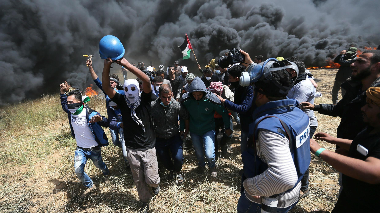 Los palestinos evacúan al periodista palestino Yasser Murtaja, de 30 años, herido de muerte durante los enfrentamientos con las tropas israelíes en la frontera entre Israel y Gaza, el 6 de abril de 2018.