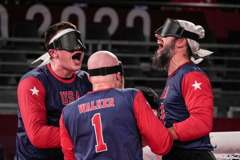 Les Américains Calahan Young (à gauche), John Kusku (à droite) et Daryl Walker (au centre) célèbrent après avoir infligé une première défaite en cinq ans au Brésil 8-6 lors de leur affrontement dans le groupe A de goalball jeudi