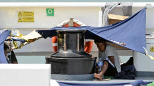 Des migrants à bord du bateau Diciotti s'abritent sous des bâches en attendant d'être fixés sur leur sort, le 23 août 2018.
