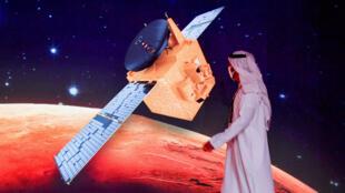 """مواطن إماراتي يمر من امام ملصق يحمل صورة مسبار """"الأمل"""" في مركز محمد بن راشد للفضاء في دبي في 19 تموز/يوليو 2020"""