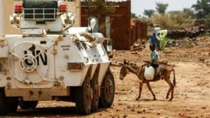 صبي سوداني يمتطي حمارا يمر بالقرب من عربة مصفحة تابعة للقوة المشتركة للأمم المتحدة والاتحاد الأفريقي في دارفور بتاريخ 19 حزيران/يونيو، 2017