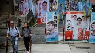 Un couple de personnes âgées passant devant les affiches de campagne des élections législatives à Hong Kong, le 4 septembre.