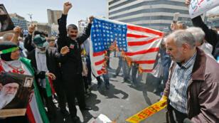 Des manifestants iraniens brûlent un drapeau américain improvisé lors d'un rassemblement dans la capitale, Téhéran, le 10mai2019.